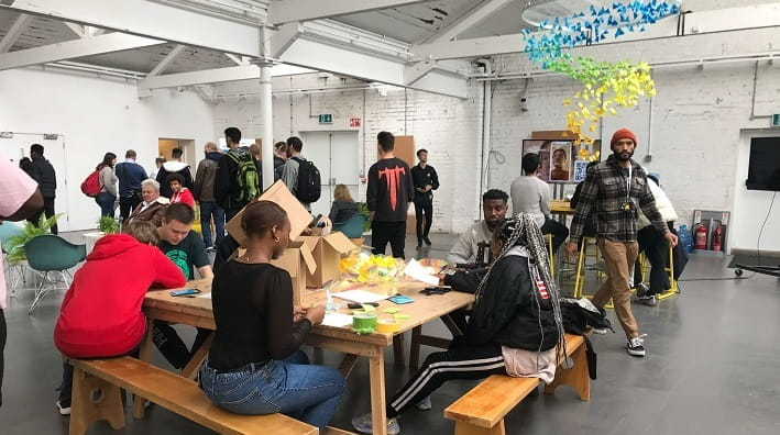 Shot of room with a table of young people in the foreground partaking in interactive activities